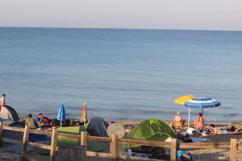 turisti in spiaggia e tende