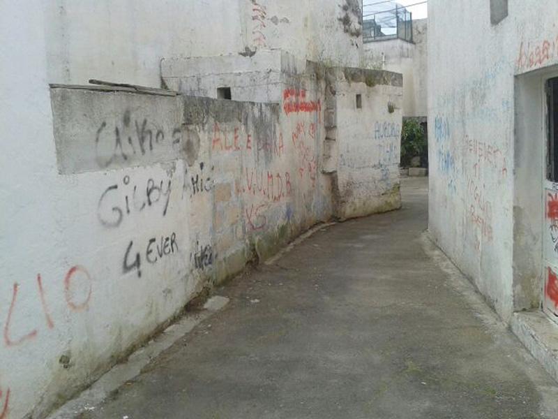 Un vicolo del centro storico di Taviano deturpato da scritte
