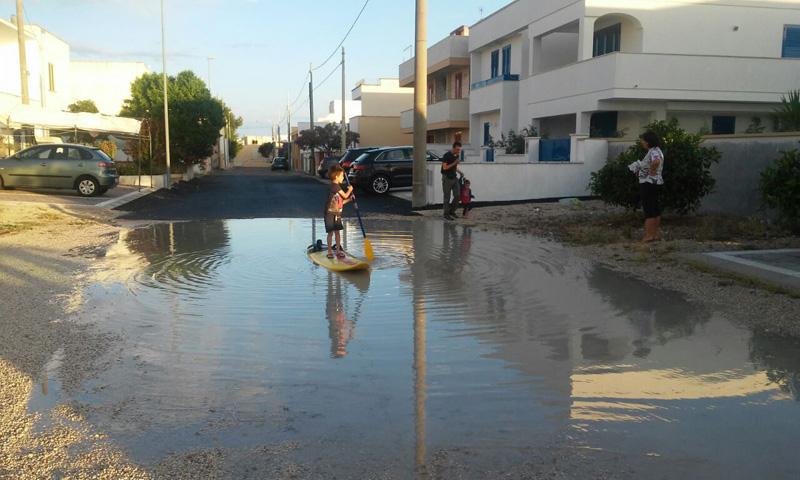 lido marini, bambino gioca nella strada allagata