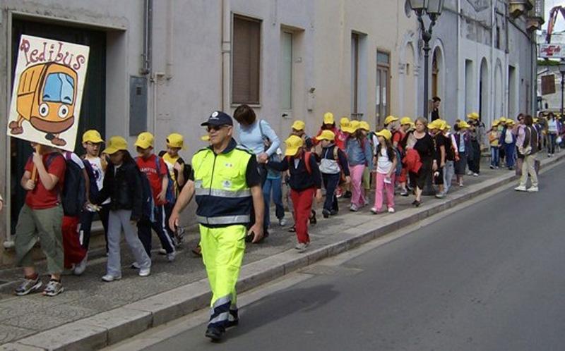 Bambini della scuola primaria, scortati da volontari adulti, raggiungono con la massima sicurezza la loro scuola a piedi